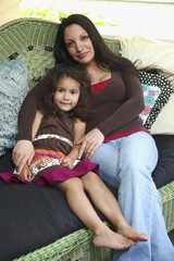 Mother sitting on sofa with daughter
