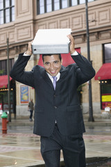 Businessman covering head with briefcase in rain