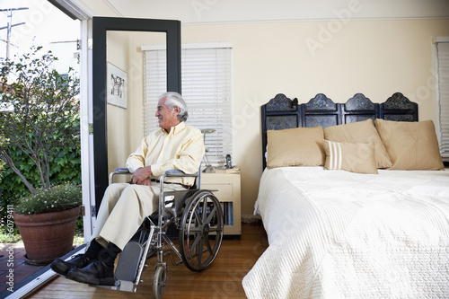 Elderly Hispanic man in wheelchair looking out window