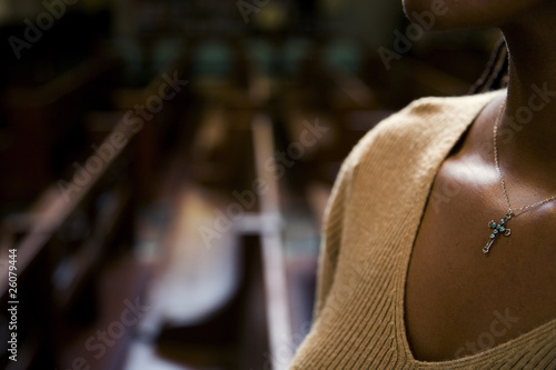 African woman wearing cross necklace in church