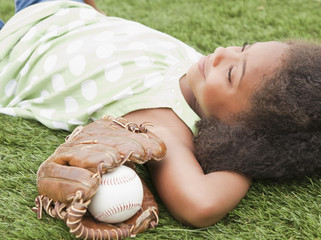 Mixed race girl laying next to baseball glove and ball