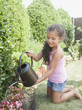 Hispanic girl watering flowers