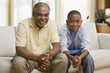 African grandfather and grandson sitting on sofa