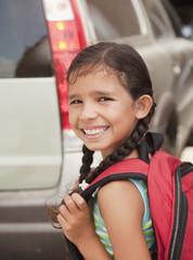 Smiling Hispanic girl carrying backpack