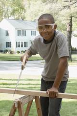 African boy sawing wood