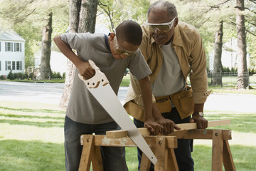 African grandfather watching grandson saw wood