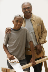 African grandfather and grandson doing carpentry