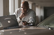 African businessman using laptop on car hood
