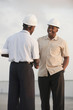 African businessmen in hard-hats shaking hands