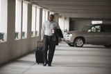 African businessman walking in parking garage with luggage