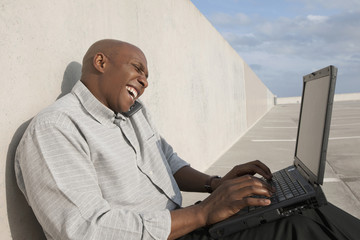African businessman using laptop in parking lot