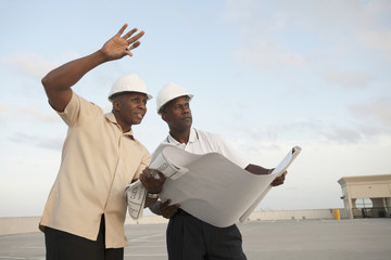 African businessmen looking at blueprints in parking lot