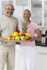 African couple holding tray of fruit