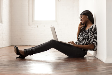 African woman using laptop and talking on cell phone in empty room