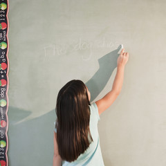 Mixed race girl writing on blackboard