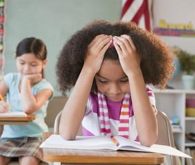 School girl reading book in classroom