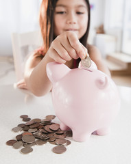 Mixed race girl putting coin in piggy bank