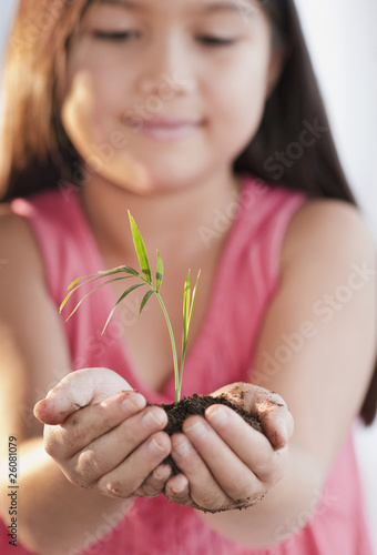 Mixed race girl holding seedling