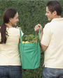 Hispanic couple carrying reusable grocery bag