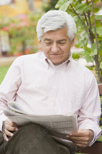 Senior Hispanic man reading newspaper