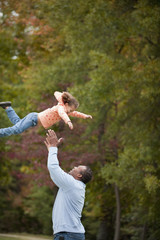 Black grandfather throwing granddaughter in the air