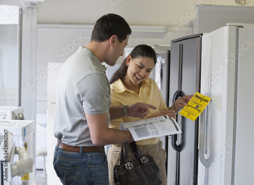 Hispanic couple shopping for refrigerator