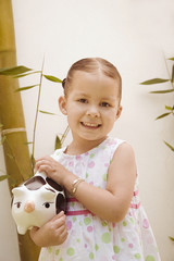 Hispanic girl holding piggy bank