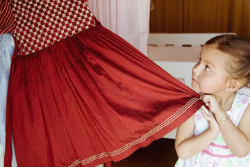 Hispanic girl taking costume from closet