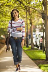 Hispanic woman walking along sidewalk