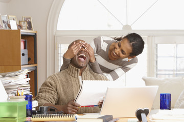 Black woman teasing husband in home office