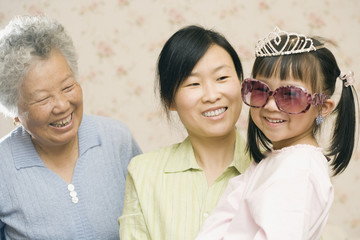 Mother and grandmother smiling at girl in princess costume