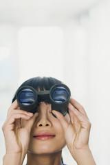 Chinese woman looking through binoculars