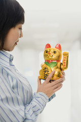Chinese woman looking at beckoning cat