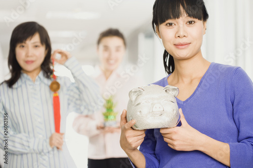 Chinese woman holding piggy bank