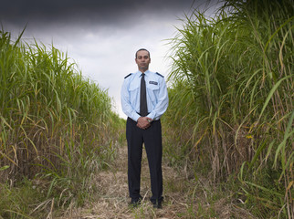 Asian man in uniform standing in field