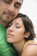 Hispanic couple hugging with eyes closed