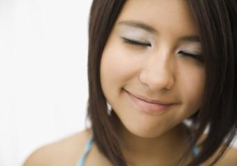 Hispanic teenage girl smiling with eyes closed