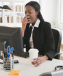 Mixed race businesswoman yawning at desk