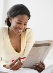 Mixed race woman reading classified ads