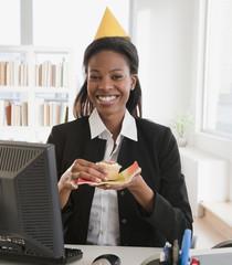 Mixed race businesswoman eating birthday cupcake