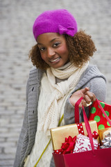 Mixed race woman carrying Christmas gifts