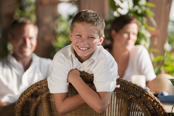 Grinning Caucasian boy in restaurant with family