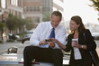 Caucasian businessman sitting on car text messaging with co-worker