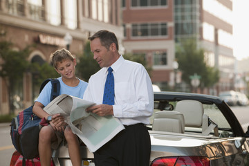 Caucasian businessman and son reading newspaper