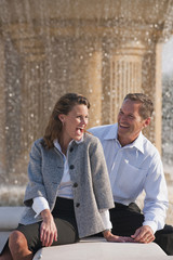 Caucasian couple laughing near spraying fountain