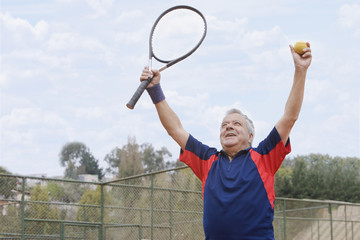 Excited senior Hispanic man playing tennis
