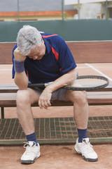 Senior Hispanic man unhappy after tennis game