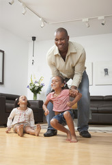 African American father playing with daughters in living room