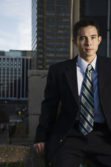 Mixed race businessman sitting on urban rooftop