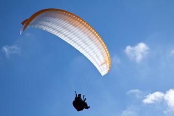 Paragliding vor Wolken und blauem Himmel